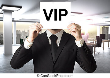 businessman hiding face behind sign vip