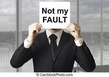 businessman in black suit hiding face behind sign not my fault failed