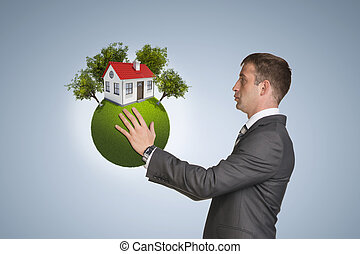 Businessman hold Earth with small house and trees