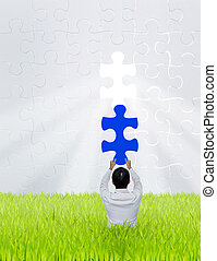 Businessman hold piece of puzzle jigsaw on green grass