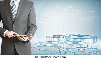 Businessman hold tablet pc. Gears and graphs
