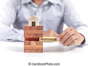businessman hold word mortgage on puzzle with wooden home model