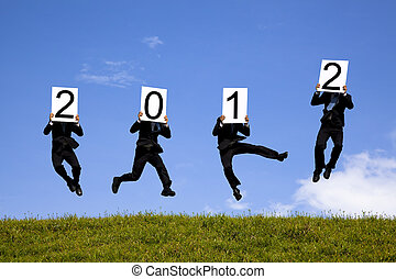 businessman holding 2012 billboard and jumping on the green field