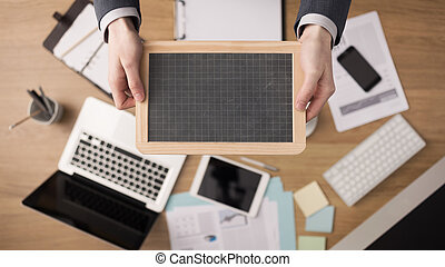 Businessman holding a blackboard