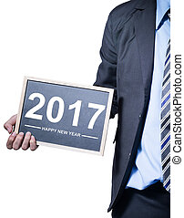 businessman holding a blackboard with text Happy New year 2017
