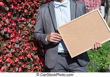 Businessman holding a Blank wood board with space for text or image at park