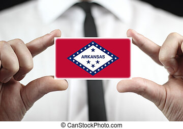 Businessman holding a business card with Arkansas State Flag