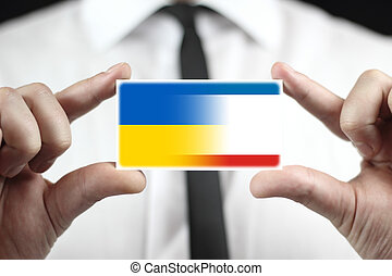 Businessman holding a business card with Autonomous Republic of Crimea and Ukraine Flag