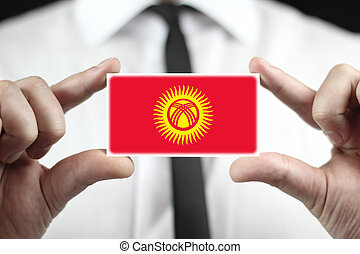 Businessman holding a business card with Kyrgyzstan Flag