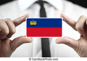 Businessman holding a business card with Lichtenstein Flag