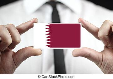 Businessman holding a business card with Qatar Flag