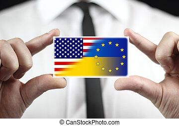 Businessman holding a business card with Ukraine, EU and USA Flag