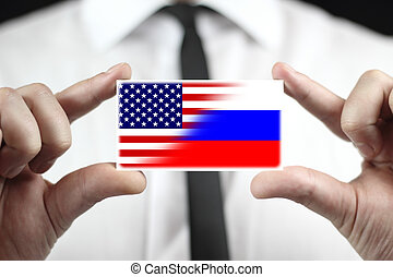 Businessman holding a business card with USA and Russia Flag