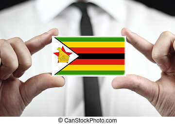 Businessman holding a business card with Zimbabwe Flag