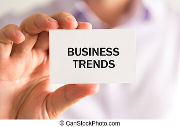 Businessman holding a card, text BUSINESS TRENDS