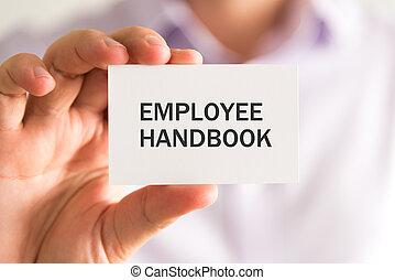 Businessman holding a card with EMPLOYEE HANDBOOK message -...