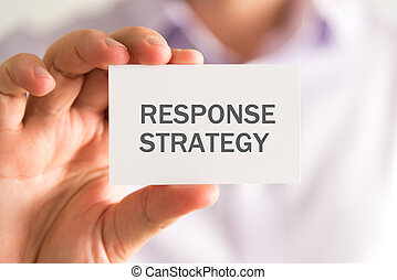 Businessman holding a card with RESPONSE STRATEGY message