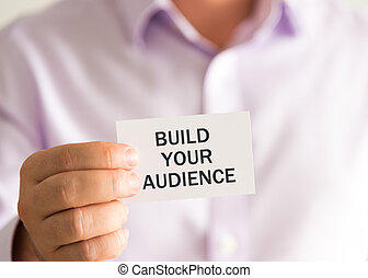 Businessman holding a card with text BUILD YOUR AUDIENCE