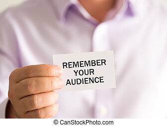 Businessman holding a card with text REMEMBER YOUR AUDIENCE