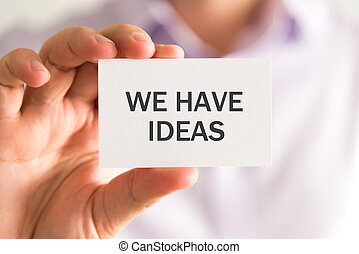 Businessman holding a card with WE HAVE IDEAS message