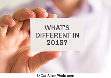 Businessman holding a card with WHATS DIFFERENT IN 2018 ? ...