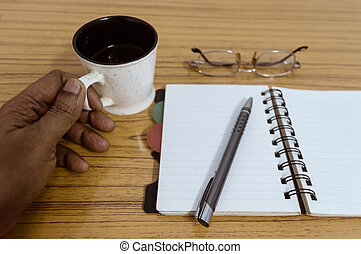 Businessman holding a cup of coffee. Business pocket planner with a eyeglass and a pen ready to note an appointment. Business still life concept with office stuff on table. Blank pages ready for mockup