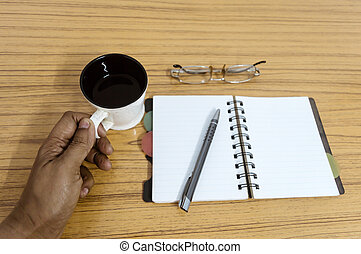 Businessman holding a cup of coffee. Business pocket planner with a eyeglass and a pen ready to note an appointment. Business still life concept with office stuff on table. Blank pages ready for text.