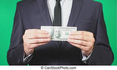 businessman holding a dollar in hand. 4k, green background, close-up, slow-motion. copy space