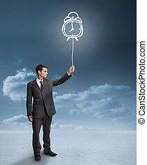 Businessman holding a floating alarm clock