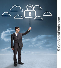 Businessman holding a floating padlock around clouds on the ...
