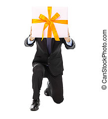 Businessman holding a gift box and kneel. isolated on white