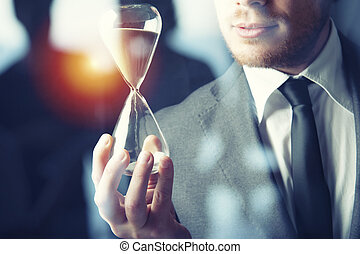 Businessman holding a hourglass. Concept of deadline in business