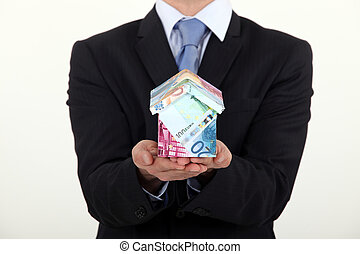 Businessman holding a house made of money