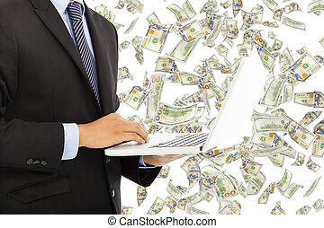 businessman holding a laptop with money rain