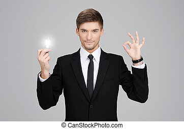 Businessman holding a light bulb and pointing