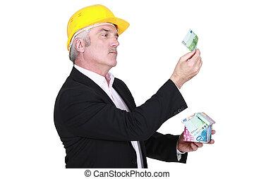 businessman holding a little house made of bills