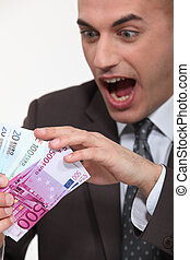 businessman holding a lot of money in cash