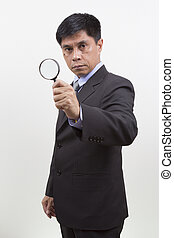 Businessman holding a magnifying glass.