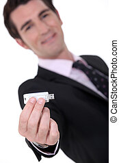 Businessman holding a memory stick