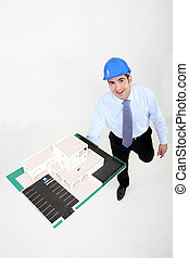 businessman holding a model of a building