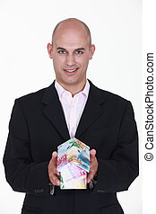 businessman holding a model of house made of money