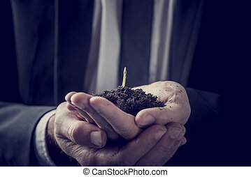 Businessman holding a plant growing in rich soil