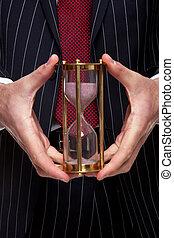 Businessman holding a sand timer