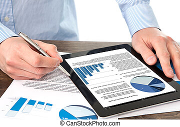businessman holding a tablet computer with graphics on a screen on the table with documents
