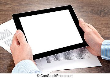 businessman holding a tablet on the table with documents