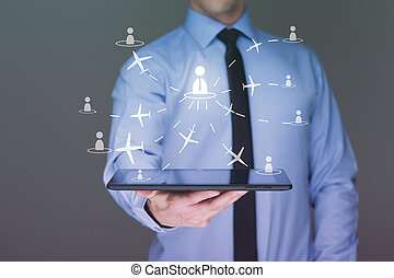 businessman holding a tablet pc. It shows planes. travel...
