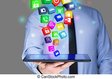 Businessman holding a tablet pc with mobile applications ...