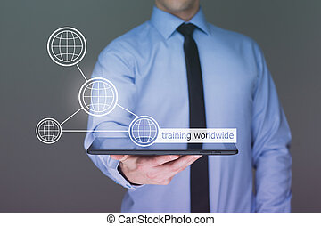 Businessman holding a tablet pc with worldwide training text...