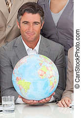 Businessman holding a terrestrial globe