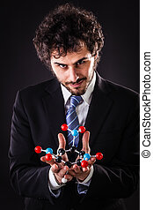 businessman holding a tnt atomic structure